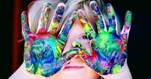 Child holding up multi-colored painted hands